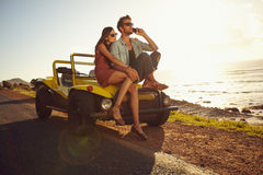 Couple on holiday on a sunny summer's day. Portrait of young couple sitting on a their car by the sea shore, with men using mobile phone. Couple on holiday on a Stock Image