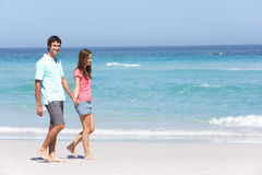 Couple On Holiday Walking Along Sandy Beach Stock Photos