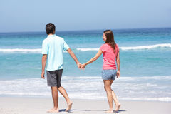 Couple On Holiday Walking Along Sandy Beach Royalty Free Stock Photos