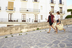 Couple on holiday walking with guidebook, holding hands royalty free stock image