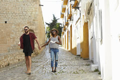 Couple on holiday walking in Ibiza streets with a guidebook Royalty Free Stock Images