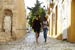 Couple on holiday walking in Ibiza streets talking Royalty Free Stock Photos