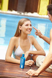 Couple in holidays applying. Happy young couple in holidays near pool applying sunscreen Stock Images