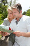 Couple on holidays looking at map Stock Photography