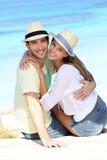 Couple on holidays sitting on sandy beach Royalty Free Stock Photo