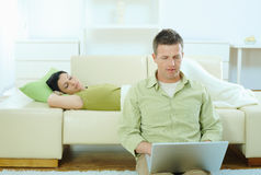 Couple at home. Man sitting on floor at home browsing internet on laptop computer, woman sleeping on sofa Stock Image