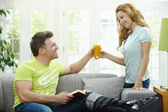 Couple at home. Man rasting his broken leg in cast on sofa at home, reading book. Woman bringing him orange juice Stock Photography