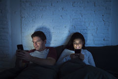 Couple at home in bed late at night using mobile phone in relationship communication problem Royalty Free Stock Images