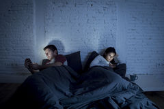 Couple at home in bed late at night using mobile phone in relationship communication problem Stock Photos