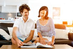 Couple at home with a book. Couple sitting on sofa and studying book together Stock Photo
