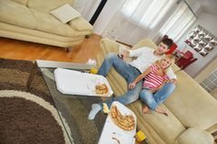 Couple at home eating  pizza Stock Photos