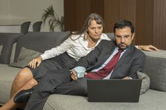 Couple at home in formalware with man working and woman watching stock photo