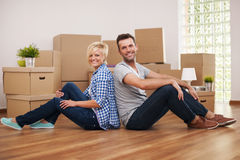 Couple at home. Happy couple sitting back to back in their new home Royalty Free Stock Photos