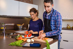 Couple in home kitchen looking recipe with a Stock Photography