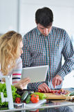 Couple in home kitchen using electronic tablet Stock Photography