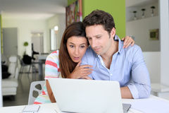 Couple at home looking at computer with an astonished look Stock Photos