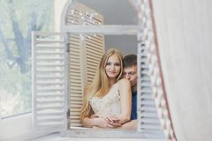 Couple at home looking in the mirror near the window. Beautiful loving family. Guy and girl cuddling together. Valentine`s day Royalty Free Stock Photos