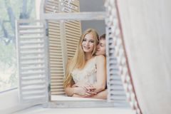 Couple at home looking in the mirror near the window. Beautiful loving family. Guy and girl cuddling together. Valentine`s day Royalty Free Stock Images