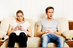 Couple at home, man watching tv woman using smartphone Royalty Free Stock Photo