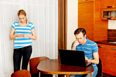 Couple at home, man working on laptop woman using mobilephone Stock Images