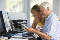 Couple in home office with computer and paperwork stock images
