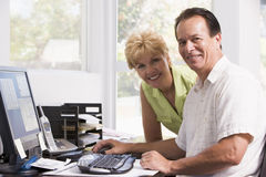 Couple in home office at computer smiling Stock Image