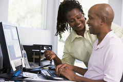 Couple in home office using computer. Couple in home office with credit card using computer