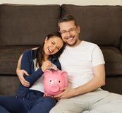Couple at home with piggybank. Cheerful young couple putting banknote in piggybank stock images