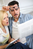 Couple at home reading news with a look of horror Royalty Free Stock Photos