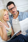 Couple at home reading news with surprised look Royalty Free Stock Images