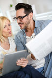 Couple at home reading surprising news Royalty Free Stock Images