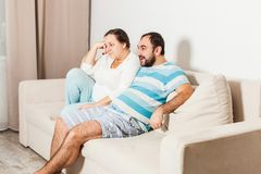 Couple at home relaxing in sofa. Young men and women watching tv royalty free stock images