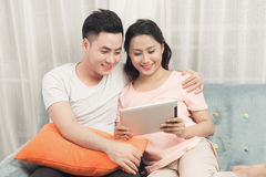 Couple at home relaxing on sofa with digital tablet.  royalty free stock photo