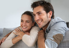 Couple at home relaxing on sofa and laughing. Couple at home relaxing in sofa royalty free stock photos