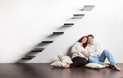 Couple at home sitting on stairs. Pregnancy Royalty Free Stock Image