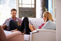 Couple At Home On Sofa In Lounge Using Digital Devices Stock Photography