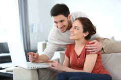 Couple at home using laptop. Couple at home shopping online with laptop Stock Image