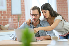 Couple at home websurfing on laptop Royalty Free Stock Image