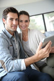 Couple at home websurfing on tablet Royalty Free Stock Photo