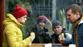 A couple of homeless men and women ask for food from visitors to a street cafe