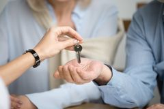 Couple of homeowners getting key to new house from realtor. Couple of homeowners getting key to new house apartment from realtor, happy real estate owners make stock photography