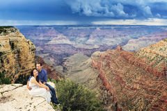 A couple on a honeymoon road trip at Grand Canyon. A couple on a honeymoon road trip sitting on the edge at Grand Canyon Stock Photography
