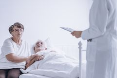 Couple of hopeful senior people. Listening to the doctor talking about test results Stock Photo