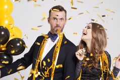 Couple celebrating New Year`s Eve. Couple with horn blower partying stock photos