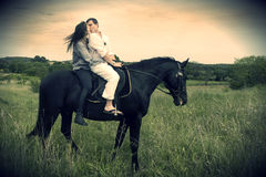 Couple and  horse in a field Stock Photo
