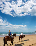 Couple of horse riders on beach. Under dramatic skies. Shot in Sodwana Bay Nature Reserve, KwaZulu-Natal province, Southern Mozambique area, South Africa Royalty Free Stock Images