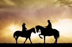 Couple on horseback at sunset Stock Photos