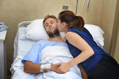 Couple at hospital room man lying in bed and woman holding his hand caring. Young sick men lying in bed at hospital room after suffering accident having his Stock Photography