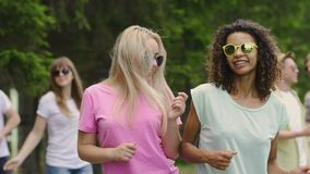 Couple of hot girls dancing with friends at open air festival, enjoying summer. Stock footage stock video footage