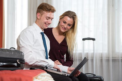 Couple in a hotel room looking at laptop computer Stock Photography